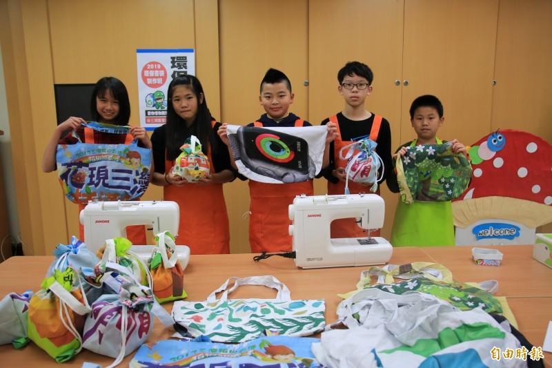 小朋友們動手DIY,將廢棄的活動旗幟回收再利用,製成美觀又實用的環保書袋。(記者鄭名翔攝)