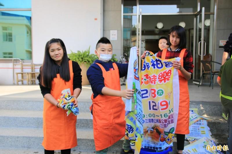 小朋友們將回收的活動旗幟清洗、曬乾,再製成環保書袋。(記者鄭名翔攝)