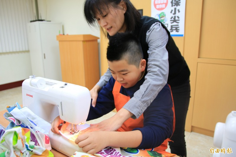 三灣圖書館館長謝淑貞教導小朋友動手做環保書袋。(記者鄭名翔攝)