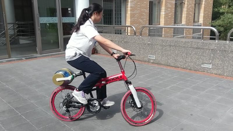 簡詩婷親自示範可邊騎車運動邊洗衣服的發明。(暨大附中提供)