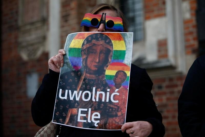 波蘭一名女子將「黑色聖母」畫像塗上象徵LGBT的彩虹旗,並印成海報張貼。圖為波蘭民眾手持海報,非文中遭逮捕女子。(路透)
