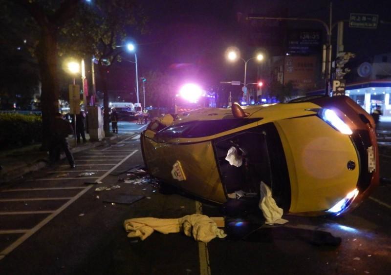 計程車側翻路中,零件散落一地。(記者許國楨翻攝)
