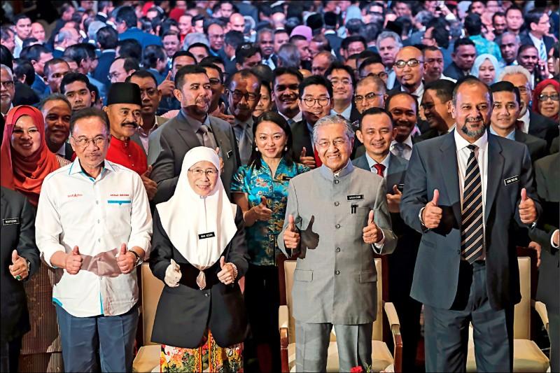馬來西亞執政聯盟希望聯盟實權主席安華(左起)、馬國副總理兼安華之妻旺阿芝莎、馬國總理馬哈地,以及馬國通訊與多媒體部長哥賓星,九日在馬國行政首都布城慶祝希盟勝選一週年的活動豎起大拇指比讚。 (彭博)