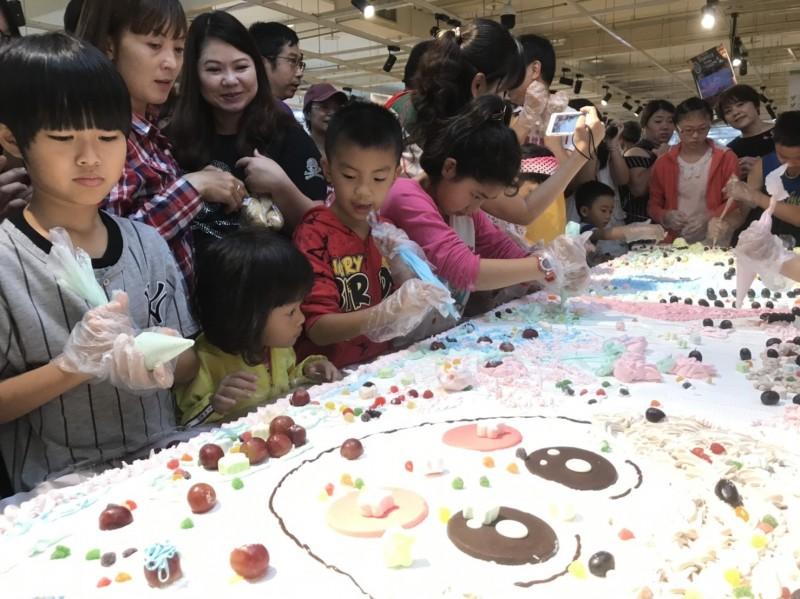 彰化家扶親子一起動手為超大蛋糕擠奶油花。(彰化家扶提供)