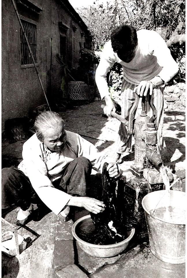 半世紀前的台灣媽媽,裹小腳蹲著洗衣服。(鐘清溪提供)