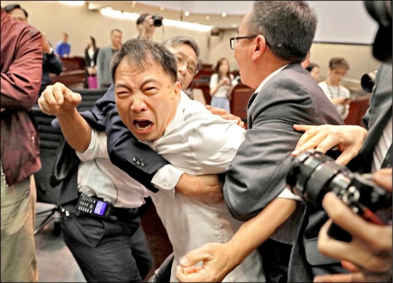 香港立法會11日進行《逃犯條例》草案審議程序,反對修法的泛民派議員發動杯葛,「民主黨」主席胡志偉(圖中)等人與建制派議員、保全人員發生肢體衝突。(美聯社)