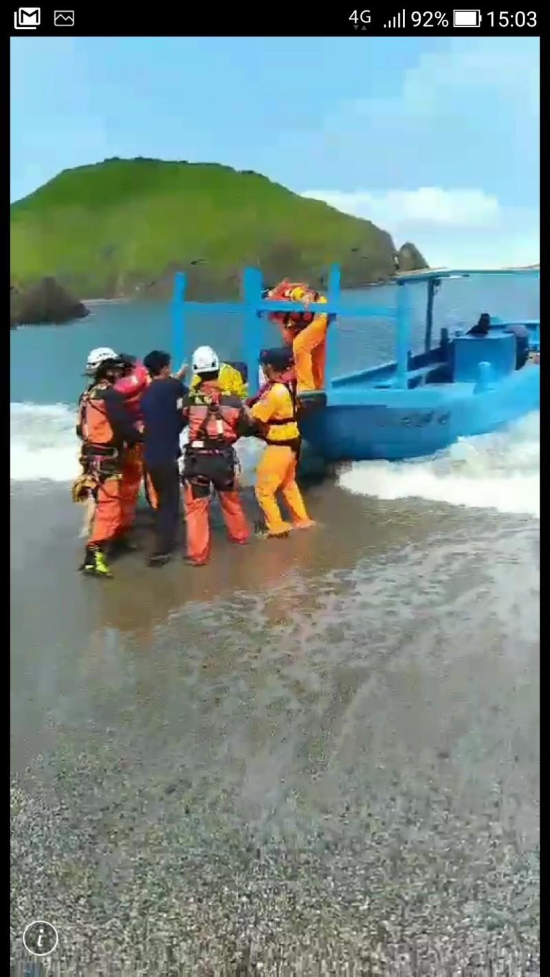 消防人員把受傷女子抬上海巡署膠笩接駁上岸。(記者江志雄翻攝)