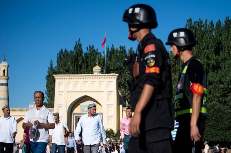 圖為在艾提尕爾清真寺附近巡邏的新疆警察。(法新社,資料照)