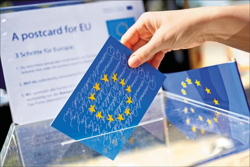 一般預料,民粹勢力將在本屆歐洲議會選舉中取得空前斬獲。圖為歐洲議會選舉的宣導巴士十三日開到德國巴伐利亞邦的阿沙芬堡(Aschaffenburg),一張畫有歐盟旗幟上十二顆星星的明信片,正被投入一個透明的票匭中。(彭博)