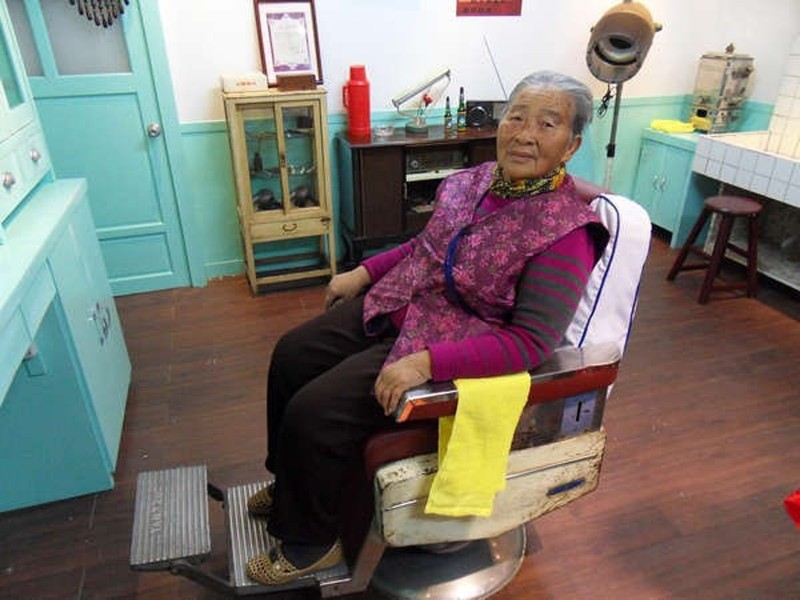張彩賢阿嬤2、3年前到「寶島」,看自己理髮廳坐在理髮椅拍的照片。(寶島時代村提供)
