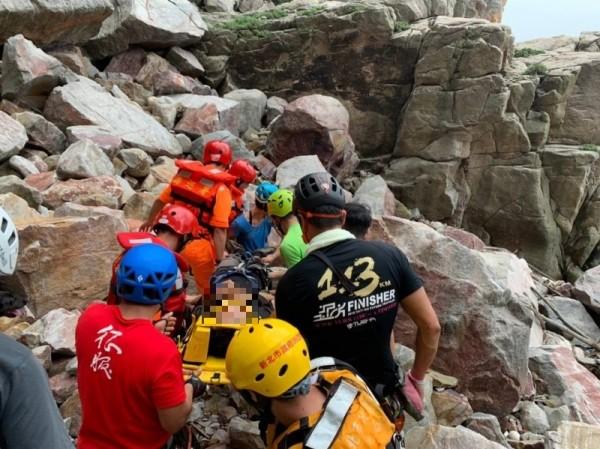 現場攀岩民眾及消防、海巡隊員合力將患者搬運上船艇(記者吳昇儒翻攝)