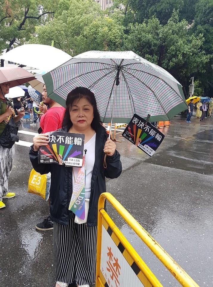 網友拍下了其中一位替同志兒子到場,在雨中微笑舉牌的母親照片,並分享了她的故事,在網路上獲得廣大迴響,有網友直言看完後「已熱淚盈眶」。(網友Jeff提供)