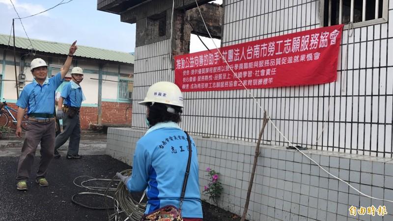 南市勞工局修繕志工今冒雨趕工。(記者王涵平攝)
