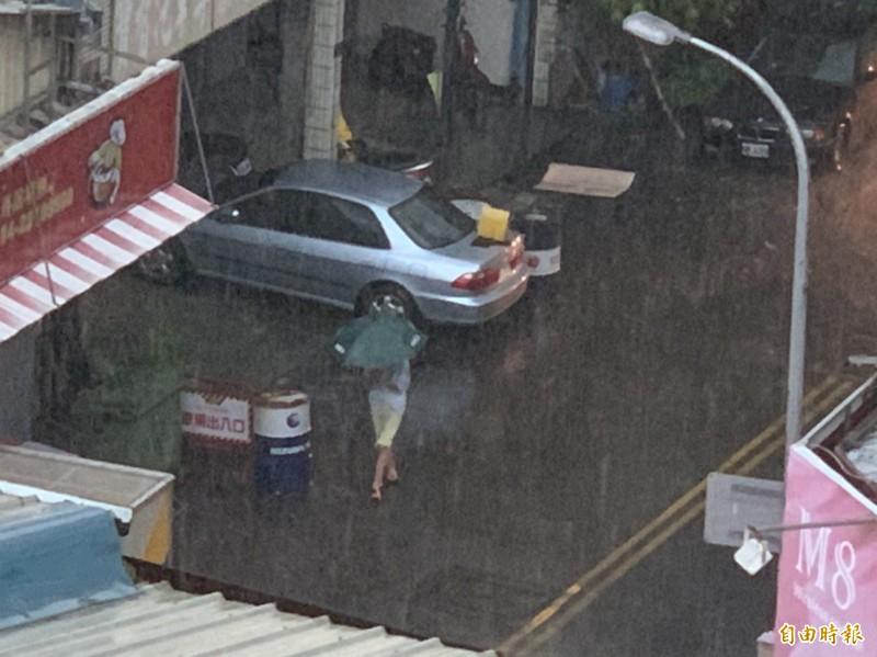 中部地區今天降下暴雨,整整下了數小時之久,民眾就算撐傘也被淋濕透。(記者湯世名攝)