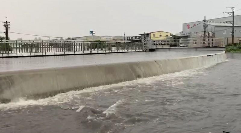 台中今天中午出現驟雨,烏日中興抽水站抽水不及,滾滾洪水溢流到路面。(記者陳建志翻攝)