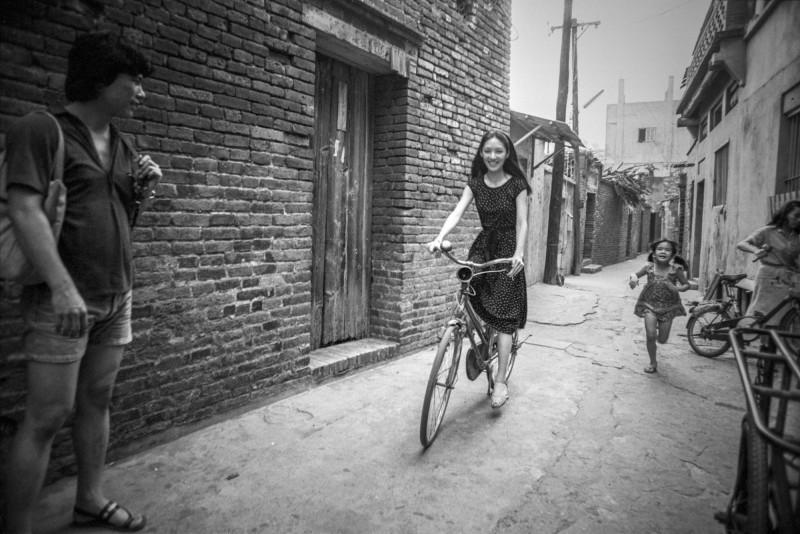 台視在1980年開拍電視劇《碧海情濤》,演員胡因夢(圖中)在拍片空檔,向民眾借單車在鹿港九曲巷開心騎車。(林彰三攝,林君勇提供)