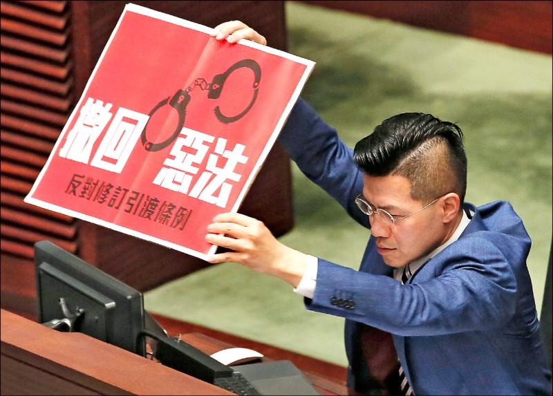 香港泛民主派立法會議員范國威四月間質詢特首林鄭月娥時,高舉「撤回惡法」標語,表達反對修訂《逃犯條例》的立場。(美聯社檔案照)