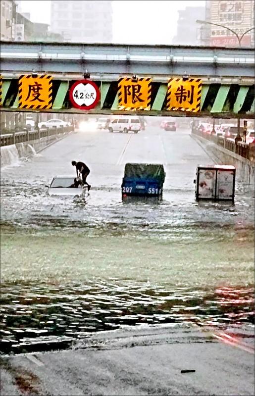 台中市國光路地下道積水過深,3輛汽車受困,駕駛爬上車頂求救。(民眾提供)