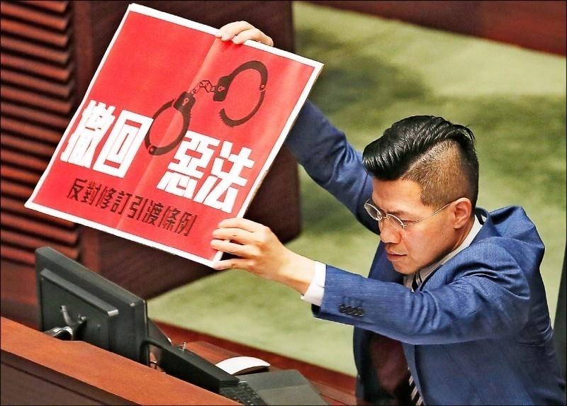港府強推「逃犯條例」引起反彈。圖為泛民議員范國威在議場中高舉「撤回惡法」標語抗議。(美聯社)