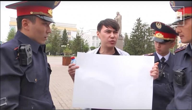 一名哈薩克男子為測試人民是否有和平抗議的權利,在大庭廣眾下,手持空白標語牌站在廣場上,果然引起警察注意,並且被帶走。(取自網路)