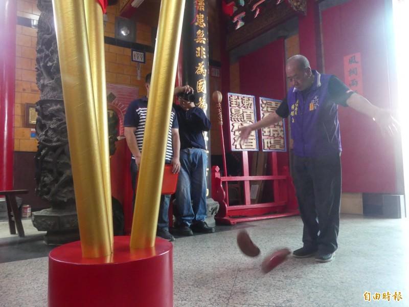金門浯島城隍廟管委會主委楊耀芸(右)在3根大型聖籤前擲筊請示水獺命名。(記者吳正庭攝)