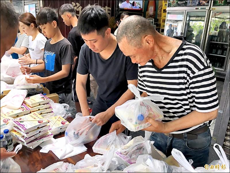 歐光榮(右一)四年來每個星期六都發出三百個便當給街友。(記者王捷攝)
