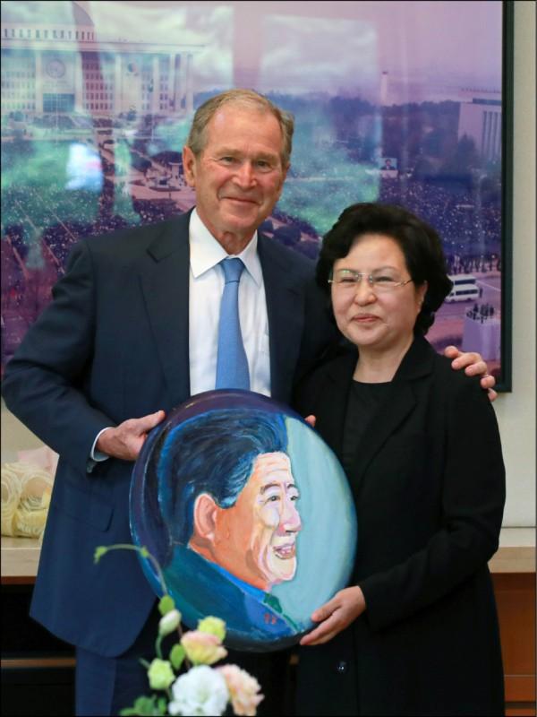 美國前總統布希23日特地赴南韓慶尚南道金海市烽下村,探望已故南韓前總統盧武鉉的遺孀權良淑(右),並致贈他所畫的盧武鉉肖像。(法新社)