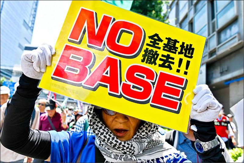 一名示威者二十五日在東京一場針對美國總統川普的抗議活動上,高舉要求美軍基地撤離日本的標語牌。(彭博)