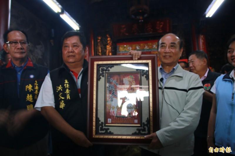 王金平(右)從拱天宮主委洪文華(左二)手中接過白沙屯拱天宮媽祖牌匾。(記者鄭名翔攝)