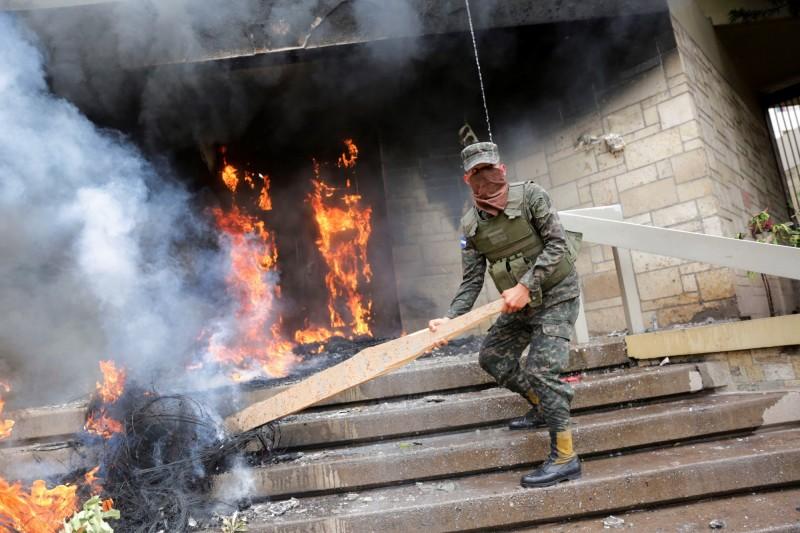 美國駐宏都拉斯首都德古西加巴大使館,遭示威者在正門堆放輪胎與易燃物後放火。圖為一名軍人正試圖滅火。(歐新社)