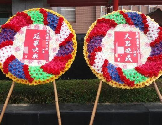 照片中只見兩座婚喪喜慶常用的立式花圈,寫著斗大「大器晚成」、「延畢快樂」。(圖取自Dcard)