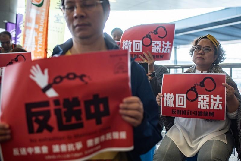 香港政府執意修訂極具爭議的《逃犯條例》,中國未來可望藉此把香港、台灣的眼中釘引渡到中國審判,引發香港各界高度反彈。圖為港人舉標語抗議《逃犯條例》,與本新聞無關。(法新社)