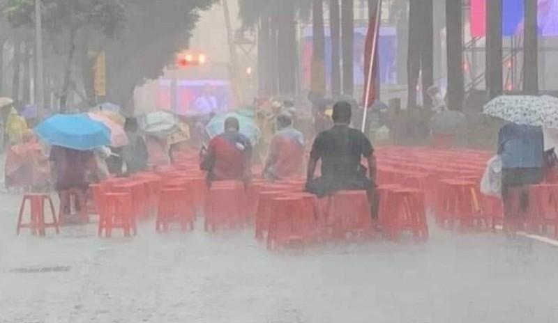 高雄市長韓國瑜首場總統造勢大會1日在凱達格蘭大道舉辦,但下午一場大雨有一位身著黑衣且沒有撐傘的男子,攜帶一支國旗坐在板凳上「堅守崗位」,事後該照片在網路上引起討論。(圖擷取自黃敬平臉書)