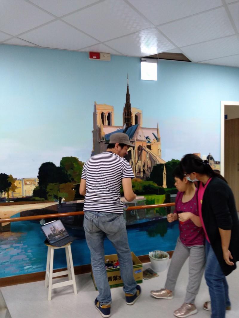 澎湖畫家許景翔2個月來當起「空中飛人」,為世光教養院的每個樓層彩繪廊道,院生好奇觀看。(記者廖雪茹翻攝)