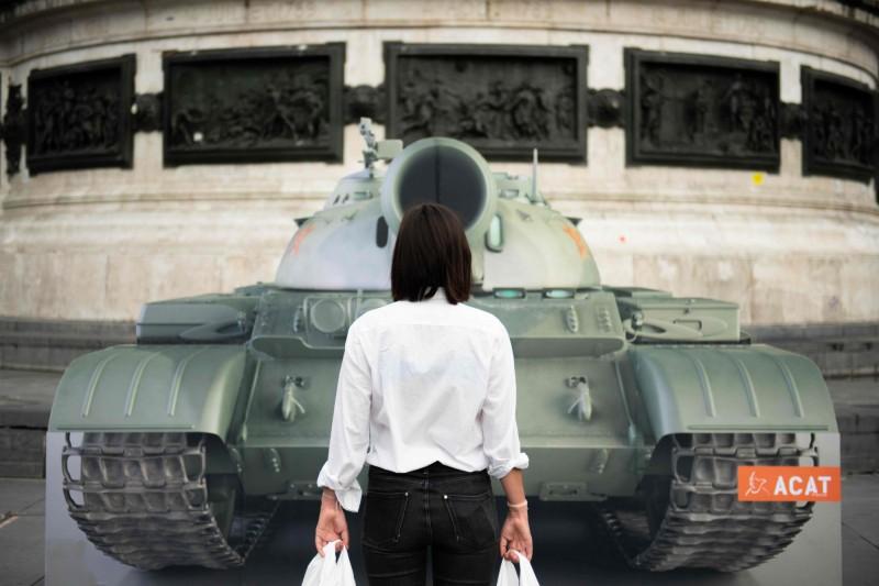 法國非政府組織基督徒廢除酷刑行動組織(ACAT)成員站在巴黎共和廣場上的假坦克前。(法新社)