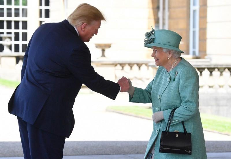 川普用了很像「擊拳」的方式與女王握手。(法新社)