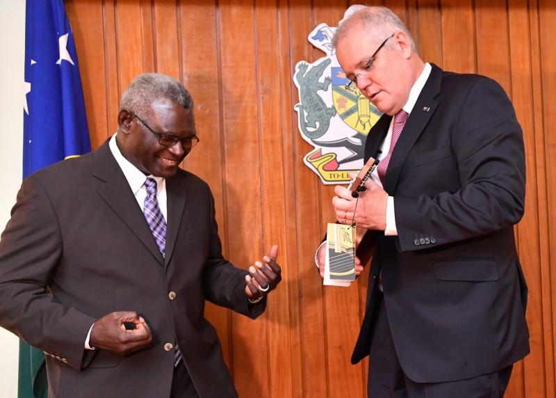 索羅門群島總理蘇嘉瓦瑞(左)3日在首都荷尼阿拉接受來訪的澳洲總理莫里森(右)致贈烏克麗麗。(歐新社)