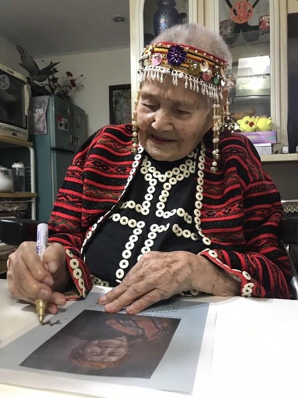 百歲的林智妹為來訪者簽名留念。(中和區公所提供)