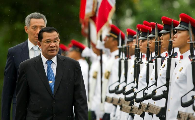 圖為柬埔寨總理韓森(Hun Sen),他身後則是新加坡總理李顯龍。(路透)