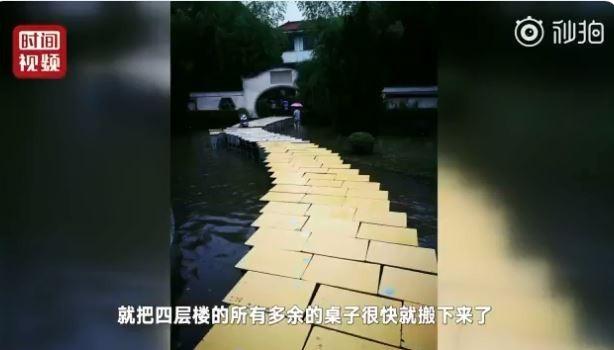 中國高考7日登場,江西省因6日發生暴雨,有中學被水淹沒,老師們搬出課桌「搭橋」,讓學生可以順利進入考場應試。(圖擷取自推特)