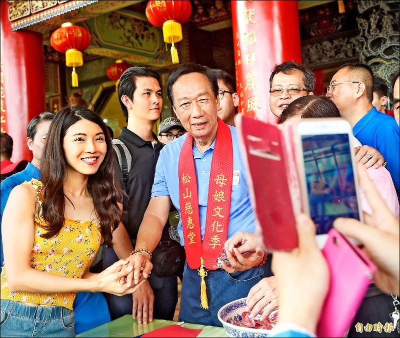 國民黨總統初選參選人郭台銘昨日前往松山慈惠堂參拜,並發放「果凍財神包」香包給民眾。(記者方賓照攝)
