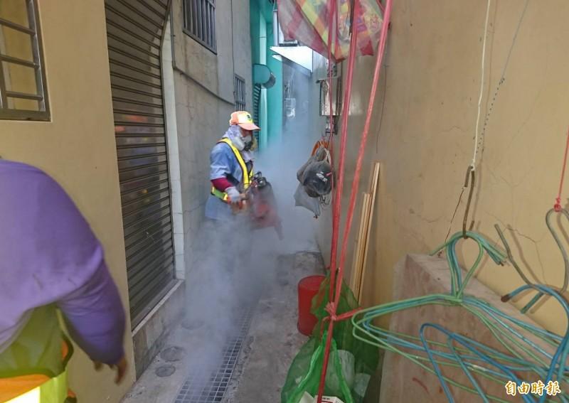鼎金里巷弄是登革熱疫區,清潔隊員忙著噴藥防疫。(記者黃旭磊攝)