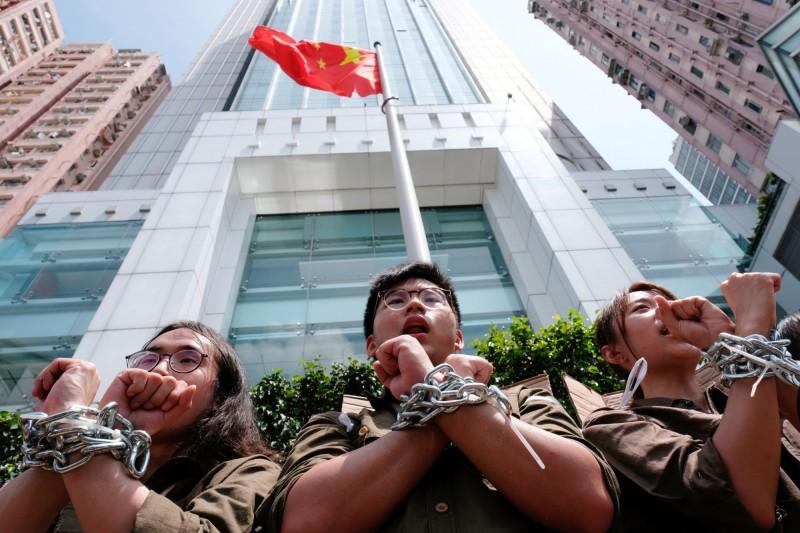 香港大專院校學生及工會組成的團體,打扮成囚犯模樣,8日下午從西區中聯辦步行至銅鑼灣。(路透)
