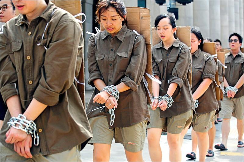 香港兩個學生組織「工學同行」與「社工學聯」的學生八日以鐵鍊綁住雙手,身穿囚衣,背著寫有如「學生支援工人罷工」等罪狀的紙牌,由西區中聯辦遊行至銅鑼灣,抗議逃犯條例的修訂。(美聯社)