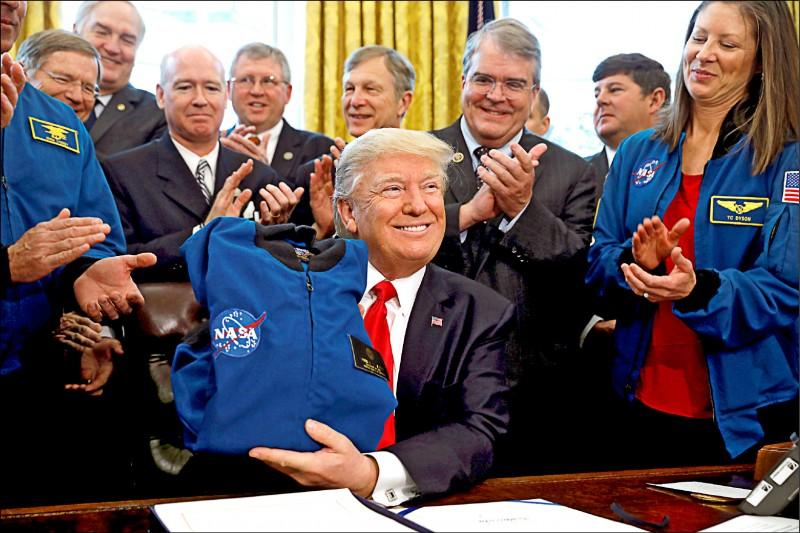 美國總統川普七日發文批評航太總署(NASA),要求NASA別再提重返月球,應該專心於火星任務。圖為川普今年三月在白宮展示他收藏的一件NASA夾克。(路透)