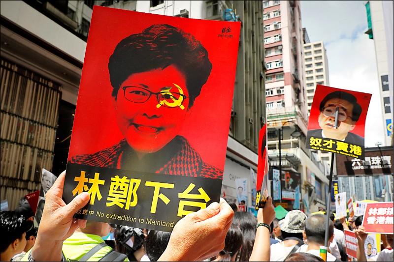 抗議者高舉要求香港特首林鄭月娥下台的海報,抗議港府修訂逃犯條例。(美聯社)