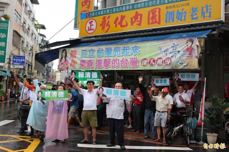 民眾穿上雨衣站在彰化肉圓店門口,高看板「賴清德2020台灣總統」迎接賴清德。(記者張聰秋攝)