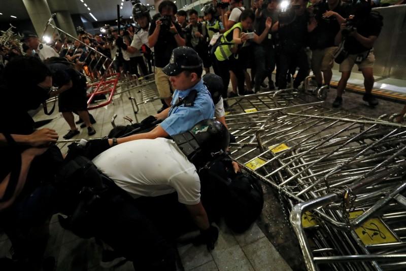 香港鎮暴警察十日逮捕推倒拒馬,要求撤回送中條例的民眾。(路透)