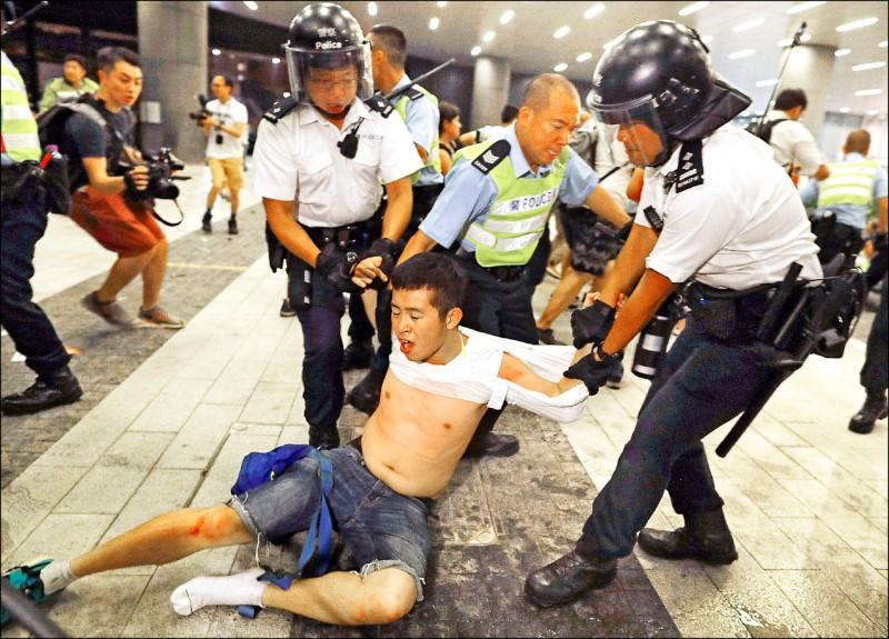 不敵優勢警力的抗議人士遭拖離現場。(美聯社)