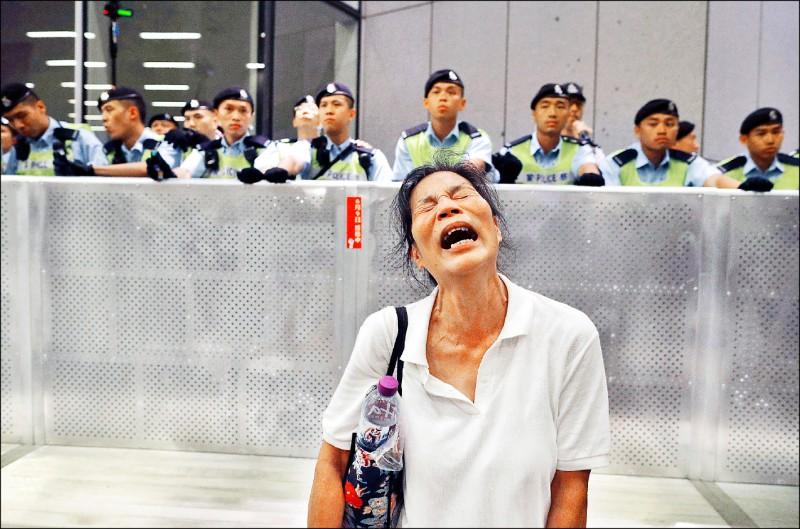 一名抗議者十日凌晨在警方強制驅離立法會外的抗議者時放聲大哭。 (美聯社)
